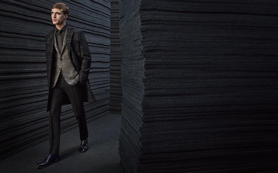 模特穿着BOSS黑色大衣和灰色印花夹克