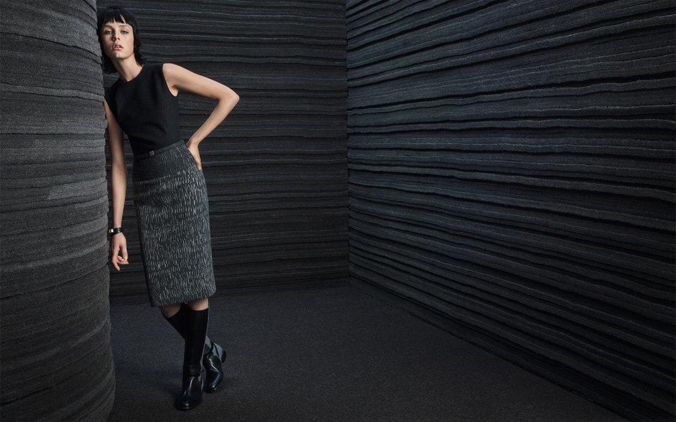 模特穿戴BOSS黑色连衣裙,漆皮靴子和手镯。