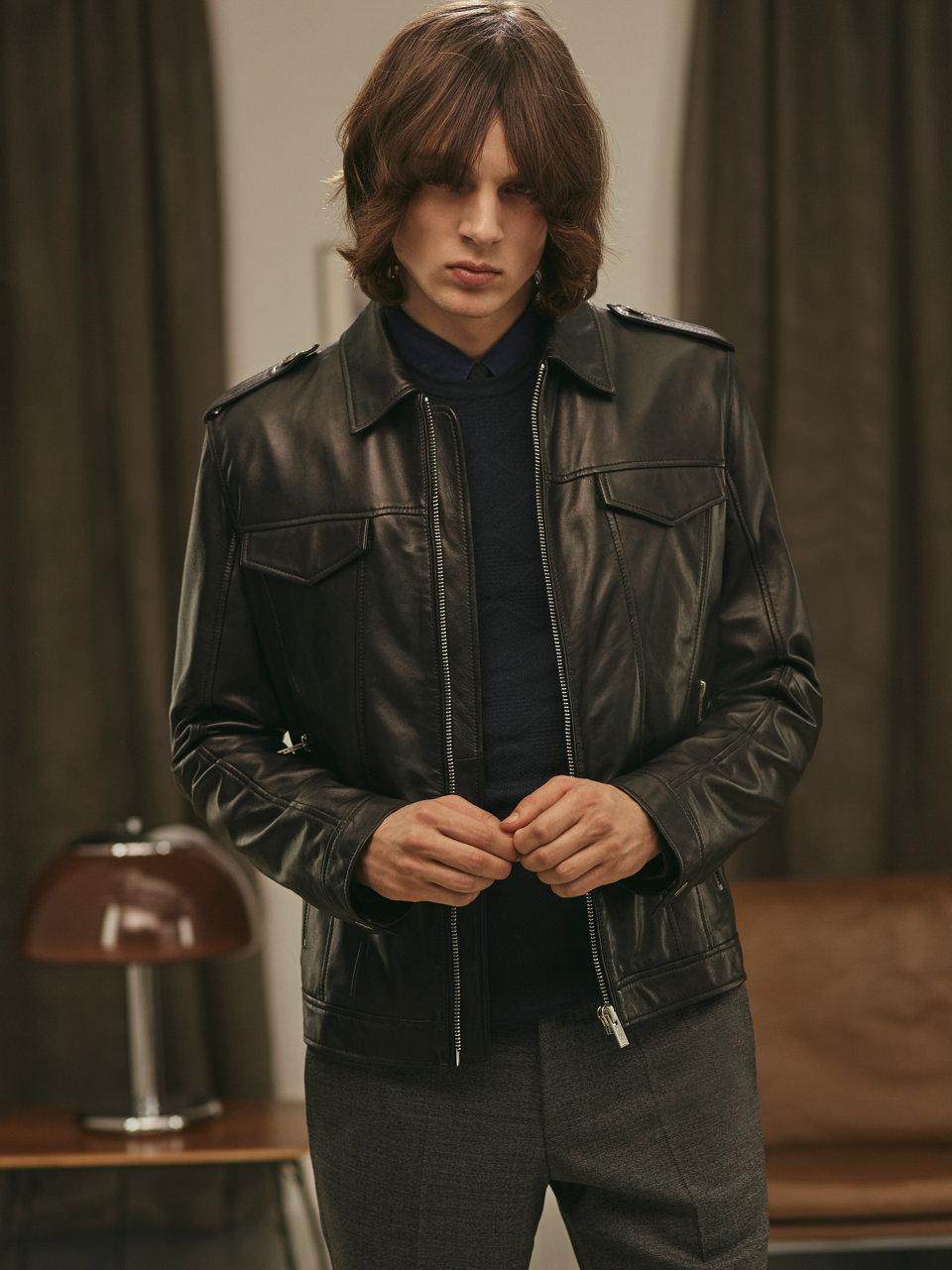 The model wears a black leather jacket byHUGO