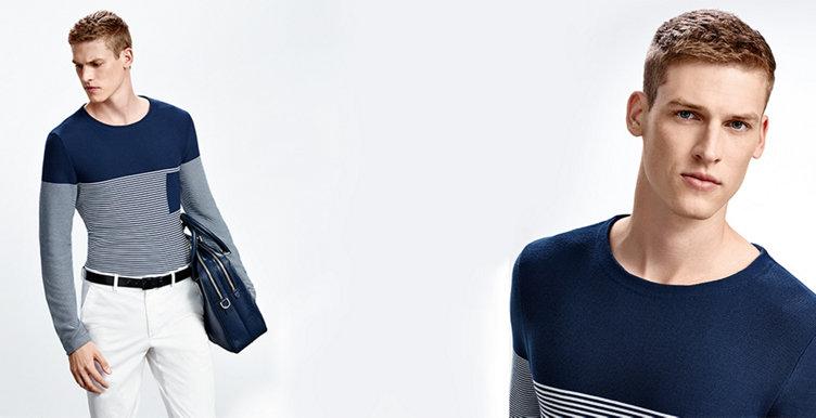Model mit Strickpullover in maritimer Optik. Kombiniert mit weißer Hose, blauer Tasche und schwarzem Gürtel.
