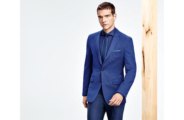 Model mit blauem HUGO BOSS Anzug. Ton in Ton abgestimmt mit blauem Hemd und Krawatte mit hellblauen Highlights.