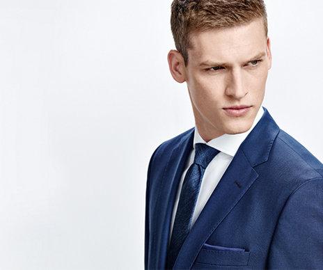 Model mit blaugemusterter HUGO BOSS Krawatte. Kombiniert mit blauem Anzug und weißem Hend.