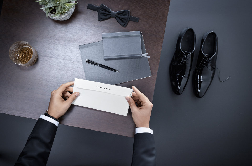 Two hands holding an envelope on top of a desk next to a bow tie with dress shoes on the floor.