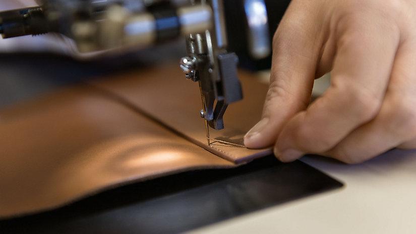 Der Boden der Tasche wird sorgfältig an die Seitenteile angenäht, um eine makellose Naht zu gewährleisten.