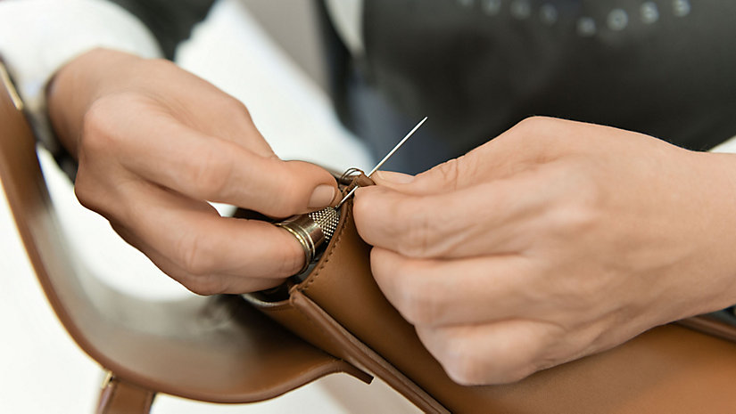 An artisan stitches the gusset of the bag by hand.