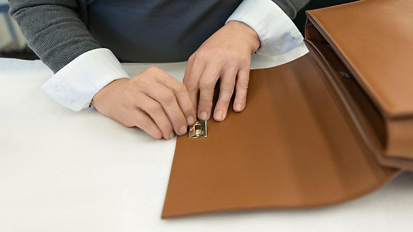 Der vom Design von Manschettenknöpfen inspirierte Verschluss wird sorgfältig befestigt.