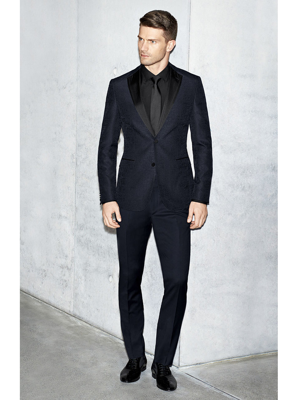 The model wears a black suit by BOSS