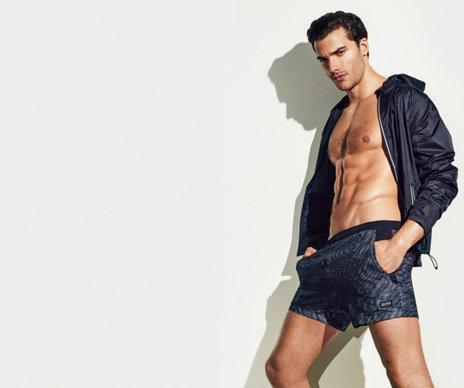 Model mit graumelierter HUGO BOSS Badeshorts und leichter Windjacke.