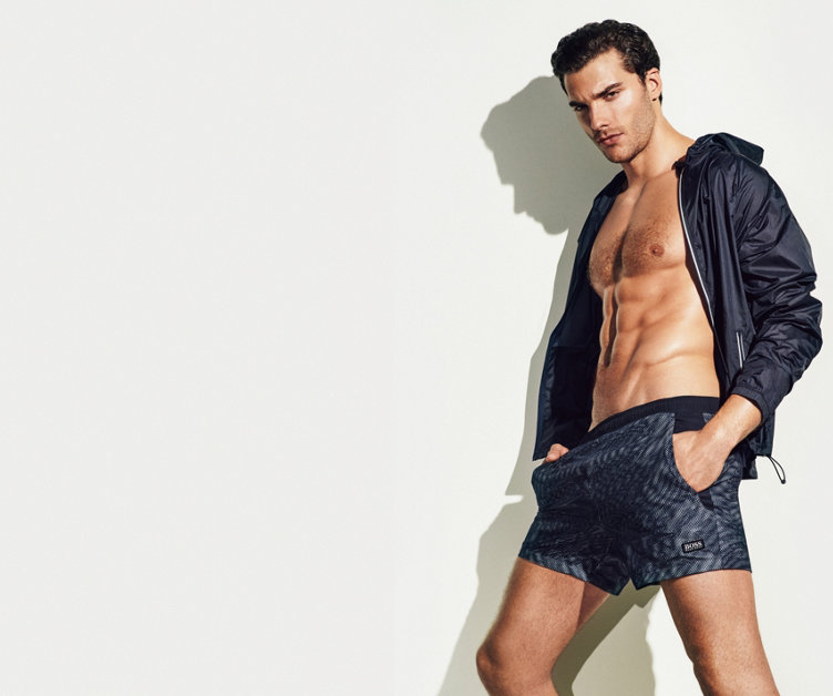 Model with tinged in grey HUGO BOSS swimshorts and a light windbreaker.