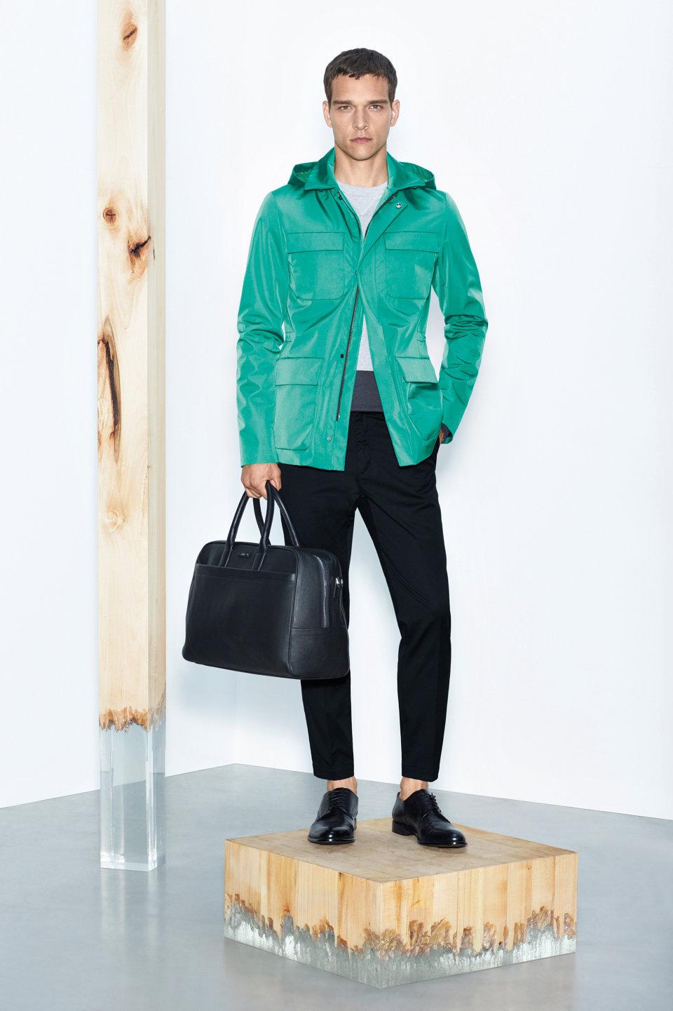 Groene jas, zwarte broek en zwarte leren tasvanBOSS