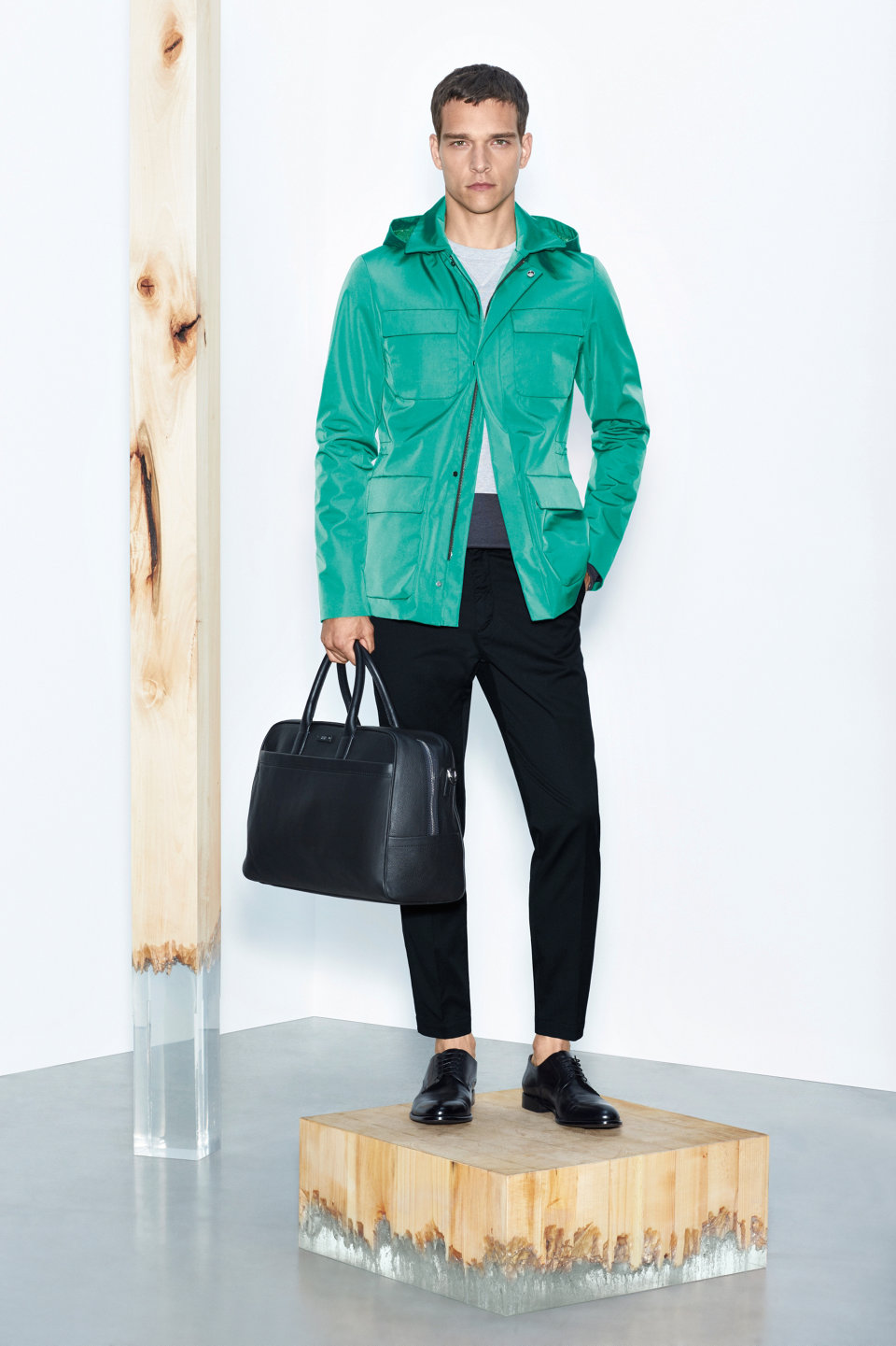 Green outerwear, black trousers and black leather bag by BOSS
