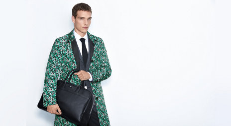 Model with reversible coat out of nylon. In black and in statement pattern green, white, black and grey. Combined with black bag and suit.