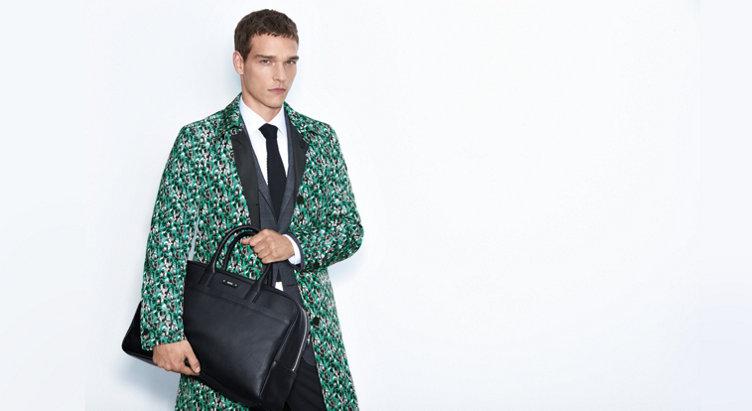 Model mit Wendemantel aus Nylon. In schwarz und Statementmuster in grün, weiß, schwarz und grau. Kombiniert mit schwarzer Tasche und Anzug.