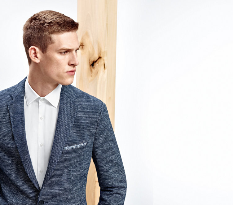 Model with modern tailored, white shirt, tinged with blue-grey tailored jackets, blue trousers and brown belt.