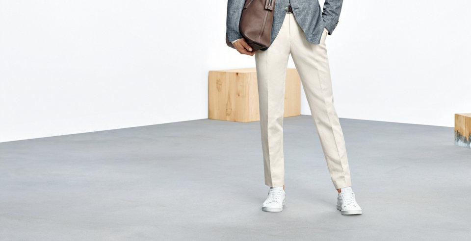 Model with cremecoloured trousers. Slim-fit with pleats. Combined with white sneakers, grey tailored jacket and brown bag.