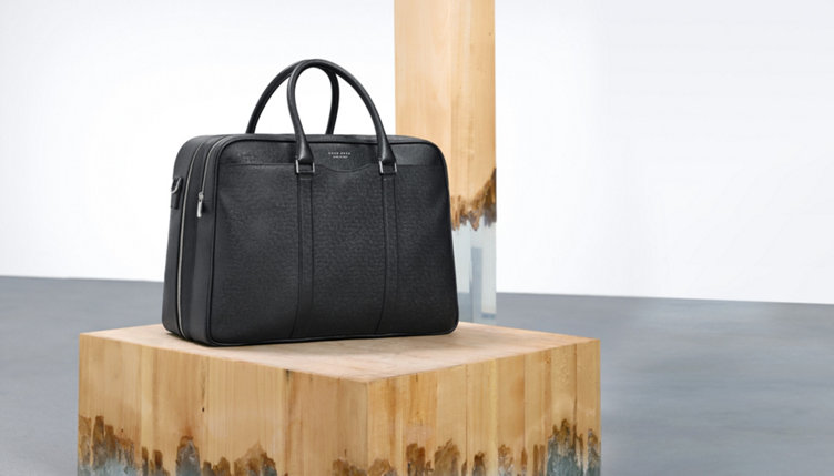 Black bag of leather for men with two pockets. With silvern zip fastener and metal elements.