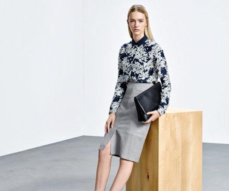 Model mit hellgrauem HUGO BOSS Pencilskirt aus Lammleder.  Der Rock wird kombiniert mit blau-grau gemusterter Bluse und schwarzer Handtasche.