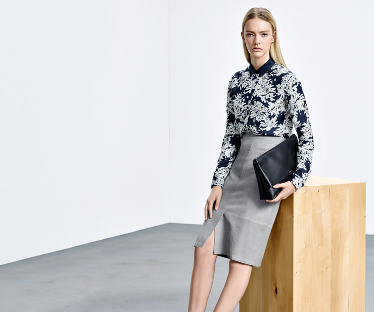 Le mannequin porte une jupe crayon HUGO BOSS gris clair. La jupe est associée à un chemisier à motif bleu-gris et un sac à main noir.