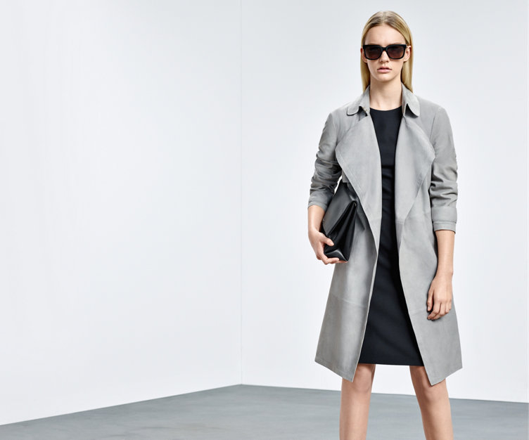 Model mit grauem HUGO BOSS Trenchcoat aus Lammleder. Kombiniert mit einem schwarzen Kleid, schwarzer Handtasche und dunkler Sonnenbrille.