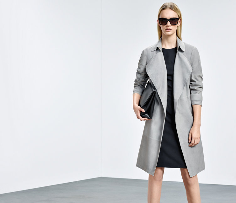 Model with grey HUGO BOSS trenchcoat out of lamb leather. Combined with a black dress, black handbag and dark sunglasses.