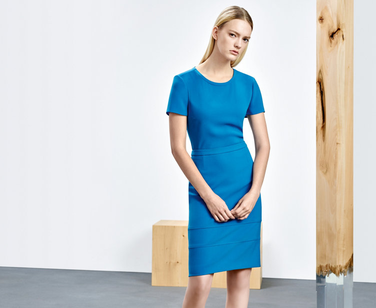 Model with seablue HUGO BOSS dress. The dress has short sleeves, tailored and waisted.