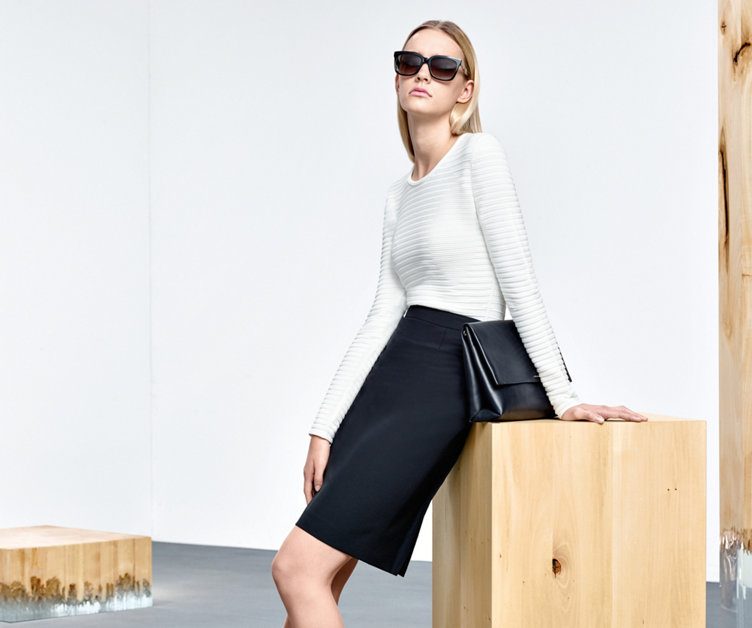 Model mit elegantem HUGO BOSS Peplum-Strickpullover in weiß. Figurnah geschnitten. Kombiniert mit schwarzem Pencilskirt und Handtasche.