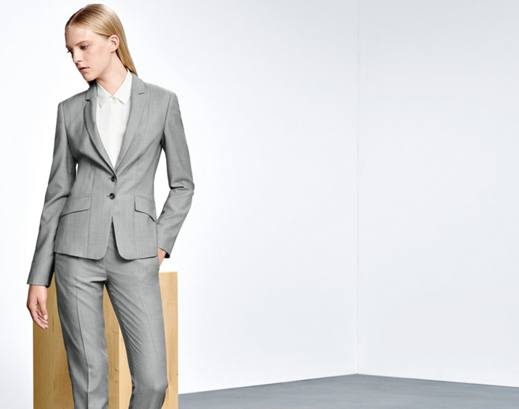 Model with HUGO BOSS suit. Lightgrey, tailored cut and pleats. Combined with a white shirt.