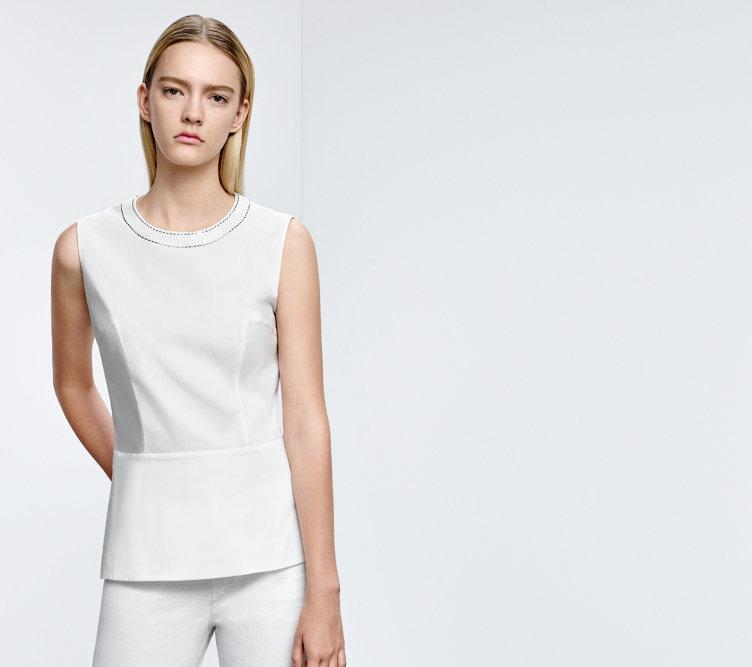 Model with a white HUGO BOSS top. Trimming neckline, tucks and a slight peplum cut.