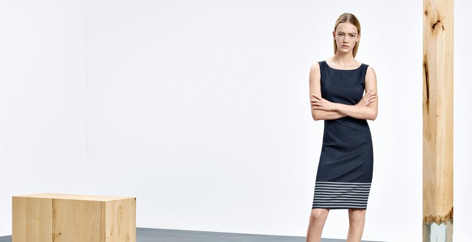 Model mit seeblauem HUGO BOSS Kleid. Das Kleid besitzt kurze Ärmel, ist figurnah geschnitten und tailliert.