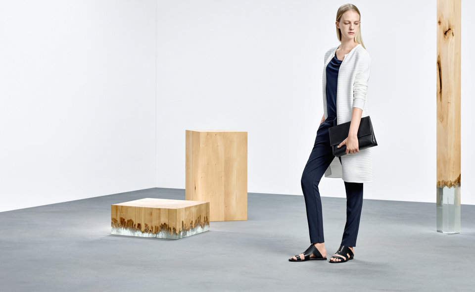 Model with flat HUGO BOSS sandals from black leather. Combined with blue trousers, white cardigan and black bag.