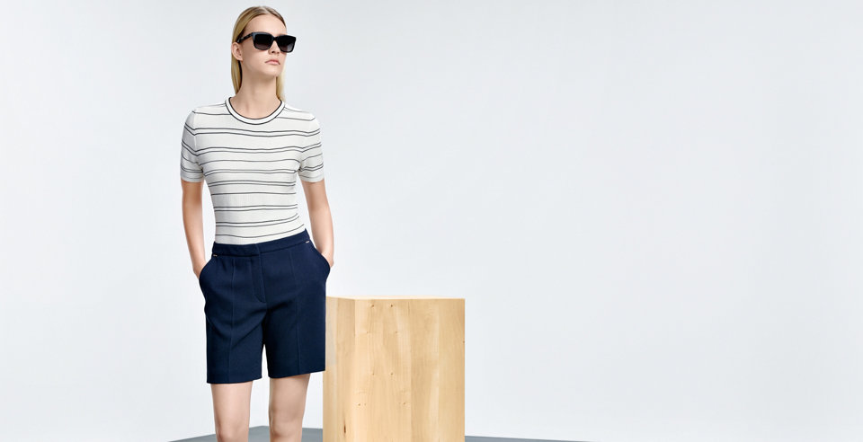 Model with fitted white-blue striped HUGO BOSS t-shirt. Combined with a blue pleat shorts and dark sunglasses.