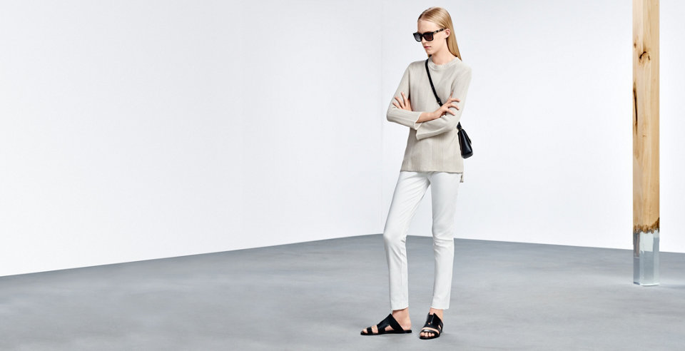 Model with white HUGO BOSS skinny trousers in modern length. Combined with beige pullover, black bag and dark sunglasses.