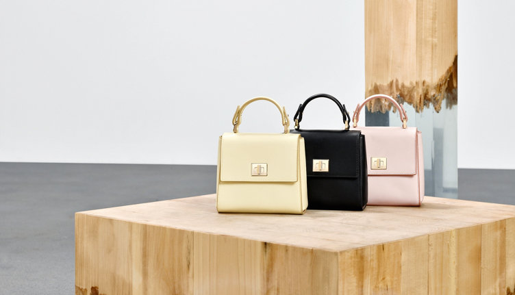 Three HUGO BOSS handbags out of leather. Shown in a row with the modern colours lightyellow, black and rose.