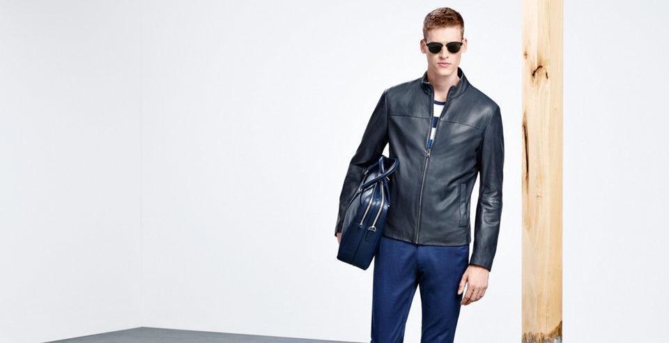 Model with black leather jacket out of soft leather, blue trousers, blue leather bag and modern sunglasses.