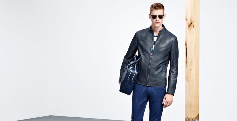 Model mit schwarzer Lederjacke aus weichem Leder, blauer Stoffhose, blauer Ledertasche und moderner Sonnenbrille.