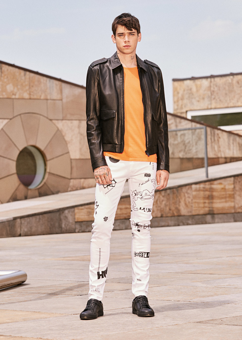 Black leather jacket, white trousers and orange sweater byHUGO