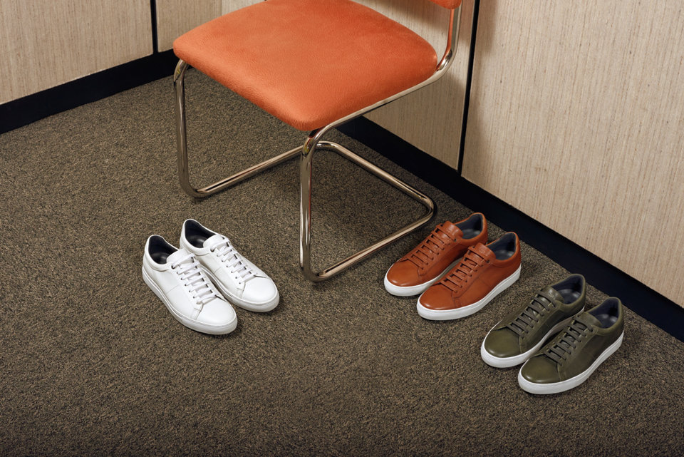 Three pairs of sneakers in white, light brown, and dark green.