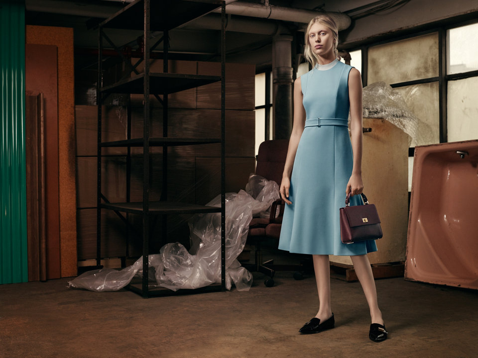 Belted powder blue dress paired with black loafers and a brown Bespoke handbag.
