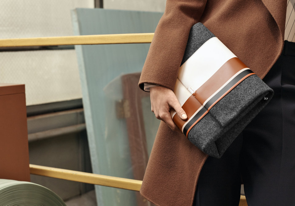 Grey clutch with white, brown and navy stripes.