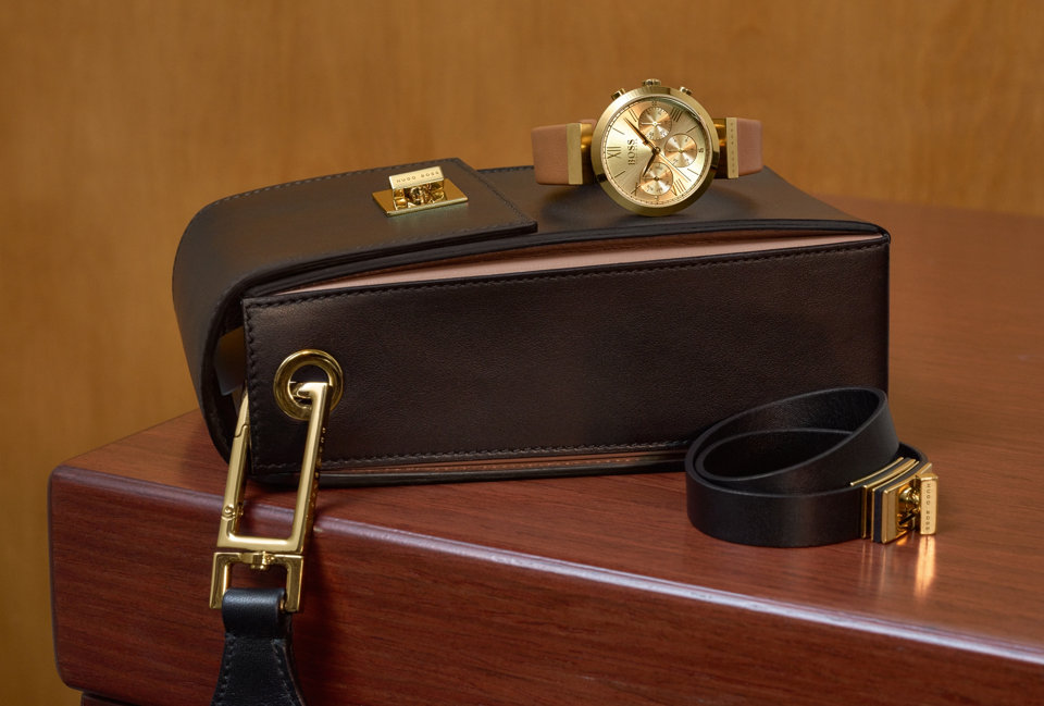 Gold Watch placed on top of a brown leather handbag next to a leather belt.