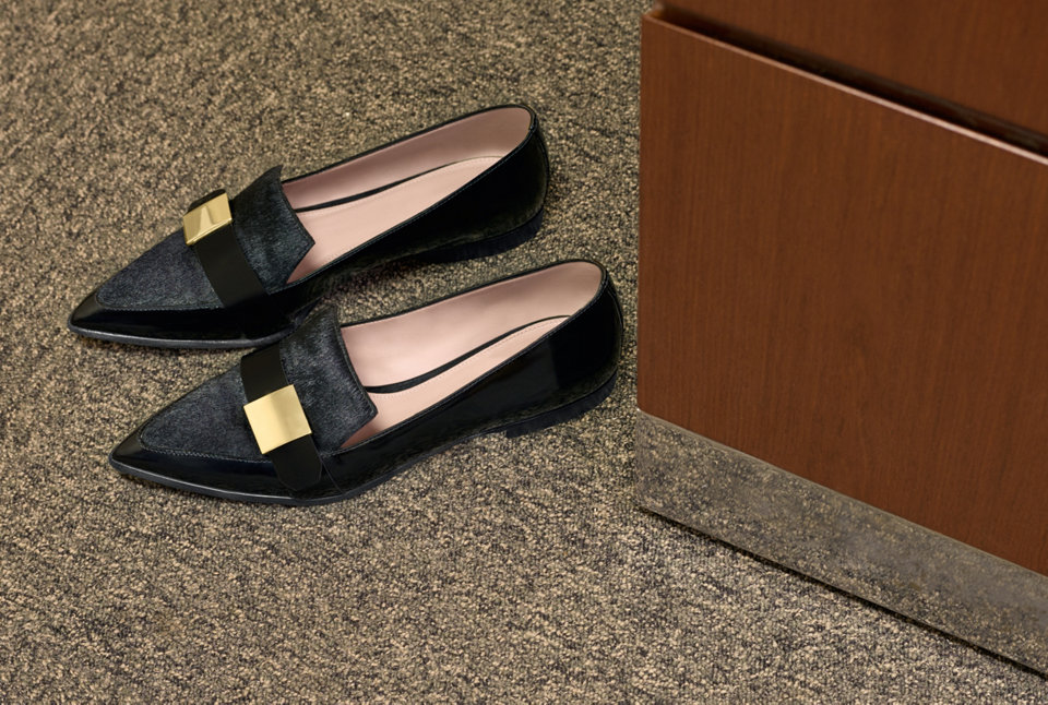 Black loafers with gold detail.