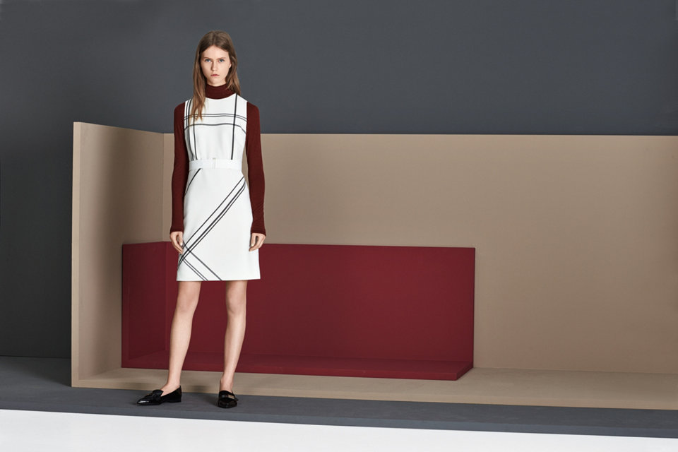 White sleeveless dress over a dark red turtle neck.