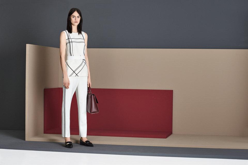 Sleeveless white blouse with a black print.