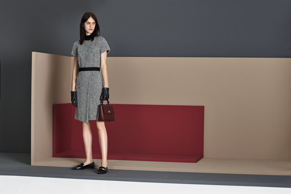 Grey short sleeve dress with a black belt, styled with black leather gloves, shoes, and a red leather handbag.