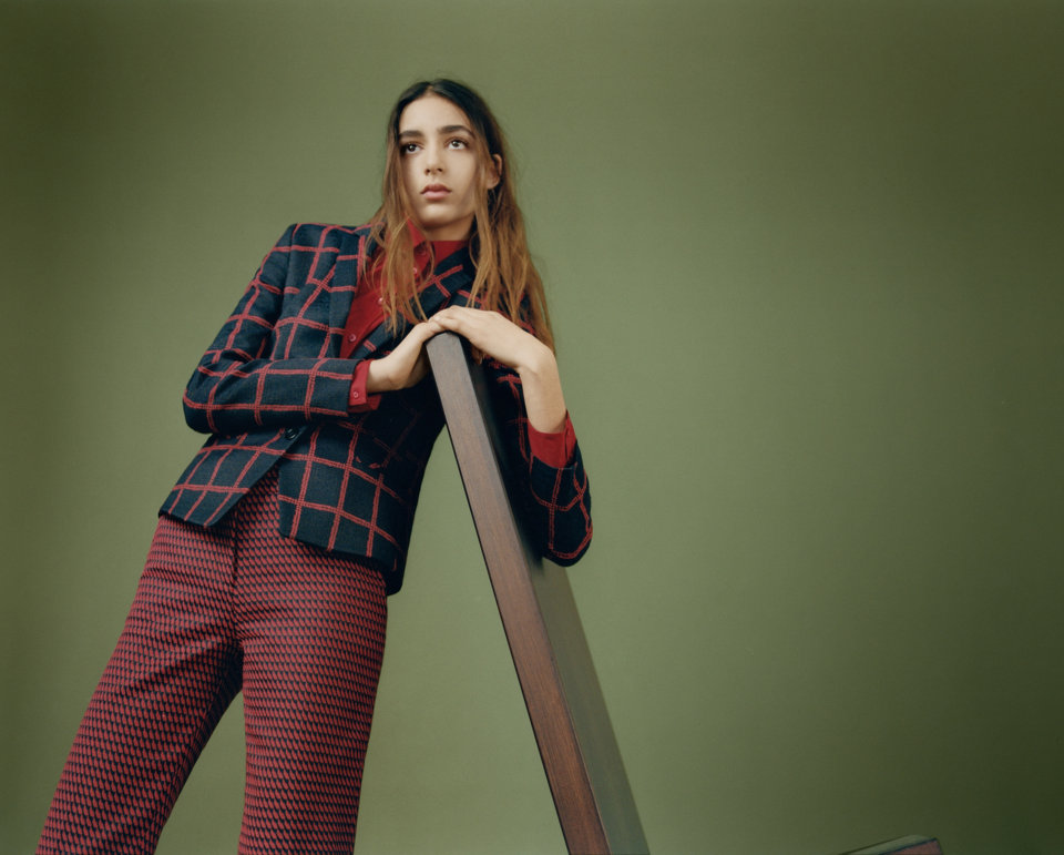 Navy blue and red checked blazer over a red button down shirt paired navy blue and red patterned trousers.
