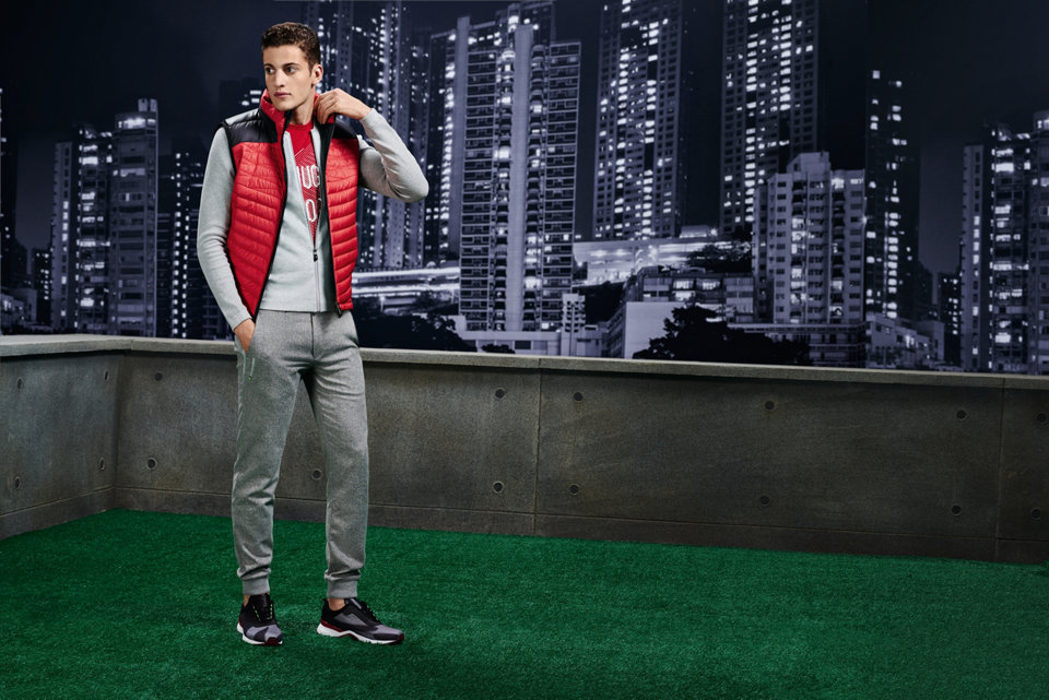 Red vest over a light grey zip-up and red graphic T-shirt paired with grey casual trousers.