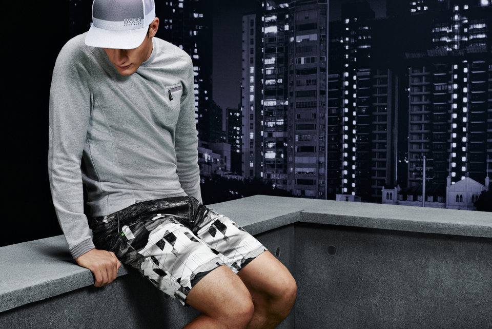 Light grey long sleeve paired with black and white patterned shorts and a white and grey hat.