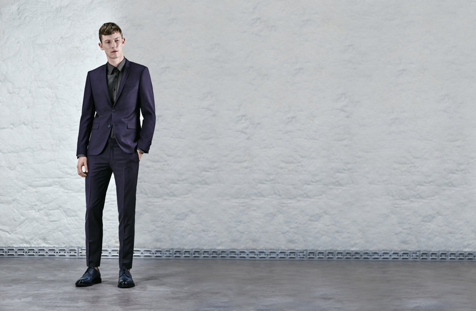 Dark blue slim-fit suit over a dark grey dress shirt.