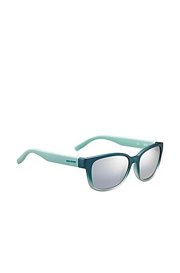 Artikel klicken und genauer betrachten! - Die Sonnenbrille von BOSS Orange mit Vollrandfassung im femininen Cat-Eye-Stil präsentiert sich im dunklen Petrol, das nach unten hin in hellere Nuancen ausläuft und durch hellblaue Bügel ergänzt wird. Verspiegelte Gläser runden das Design ab. Ansprechendes Damen-Accessoire, das optisch und durch seine leichte Tragequalität überzeugt. | im Online Shop kaufen