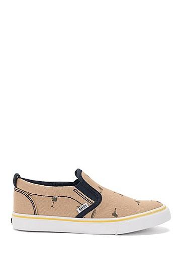 Artikel klicken und genauer betrachten! - Für einen trendigen Casual Style sind die BOSS Kids-Sneakers aus robustem Canvas die ideale Wahl. Das coole Muster mit Palmen und Surfbrettern macht die Jungen-Schuhe zum Sommer-Hit. Der typische Slipper-Look entsteht durch die runde Schuhspitze, die elastischen Einsätze und die kontrastfarbene Gummisohle. | im Online Shop kaufen